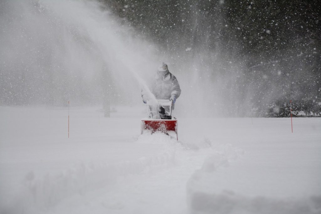 A person clearing snow from a driveway; Connecticut snow and ice slip-and-fall injuries.
